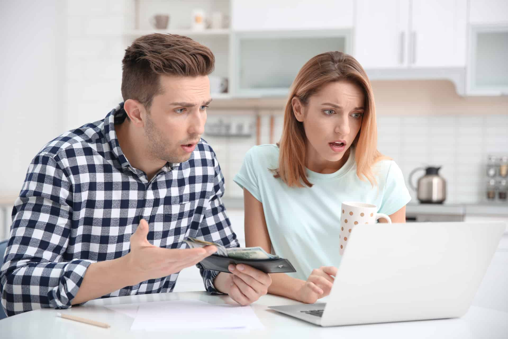 Young man holding wallet next to a woman holding a coffee cup while both are upset while looking at a computer screen