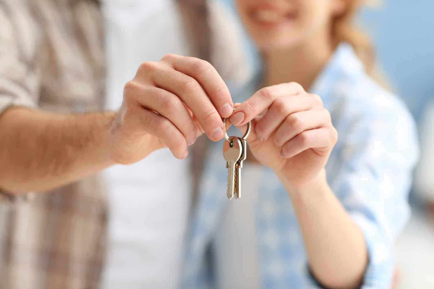 Young happy couple holding keys from their new home